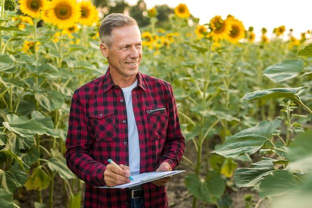 Mann, der mitteilungen auf einem sonnenblumengebiet nimmt