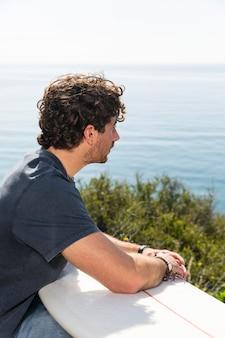 Mann, der mittleren schuss des surfbretts hält