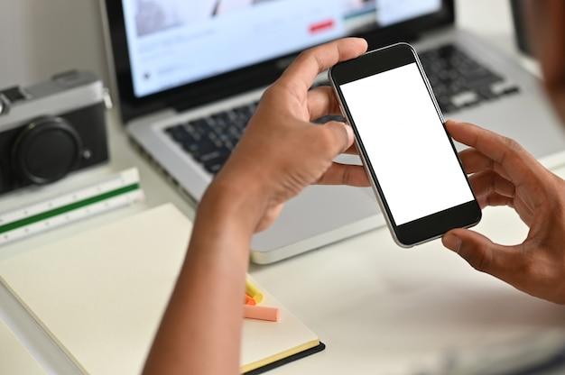 Mann, der modell smartphone auf schreibtisch verwendet