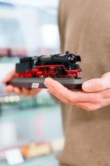 Mann, der modelleisenbahn im spielzeugladen kauft