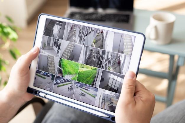 Mann, der moderne cctv-kameras auf digitalem tablet überwacht, drinnen überwachungssicherheitssystem