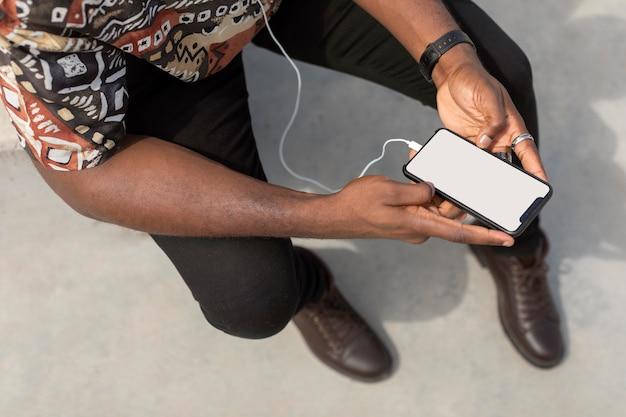Mann, der modernes smartphone mit kopfhörern verwendet