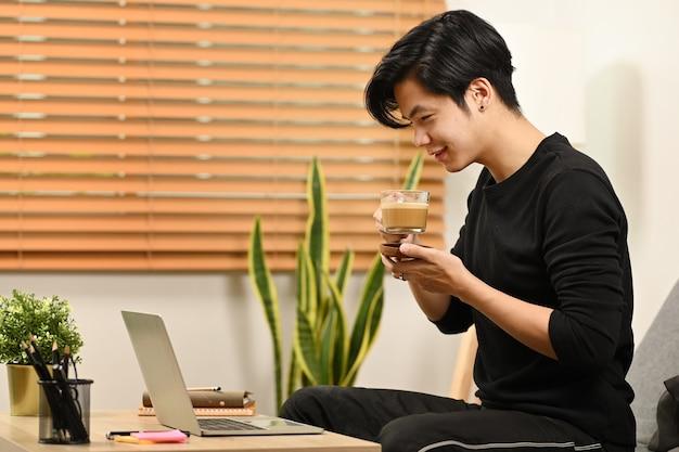 Mann, der morgens kaffee trinkt und nachrichten auf dem laptop liest.