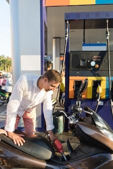 Mann, der motorrad auf stations-motorradfahrer-benzin-fahrrad tankt