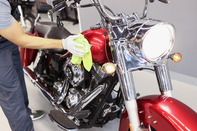 Mann, der motorrad im service-center-motorradpolier- und -waschservicekonzept säubert
