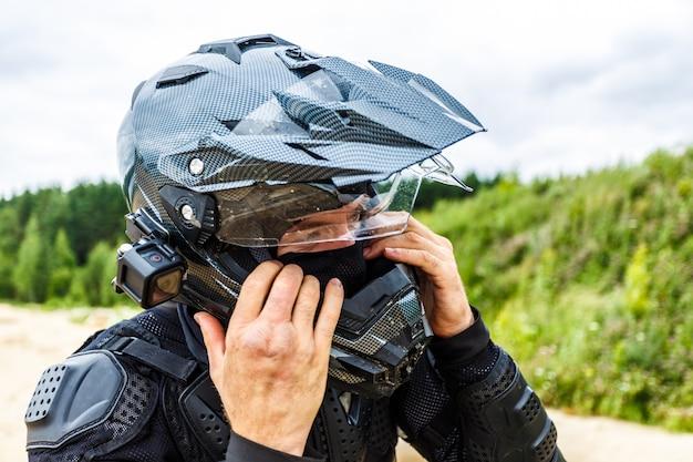 Mann, der motorradhelm auf landschaft trägt