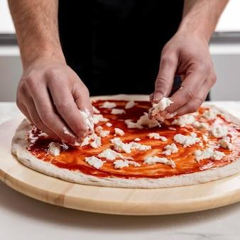 Mann, der mozzarella auf pizzateig setzt
