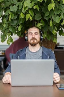 Mann, der musik an einer terrasse mit laptop genießt