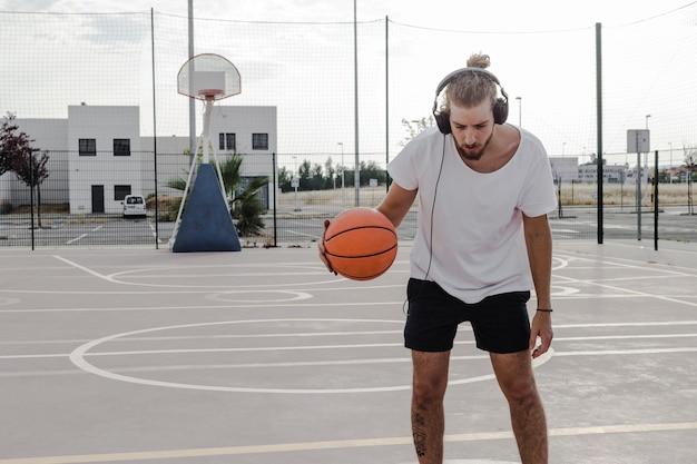 Mann, der musik beim spielen des basketballs hört