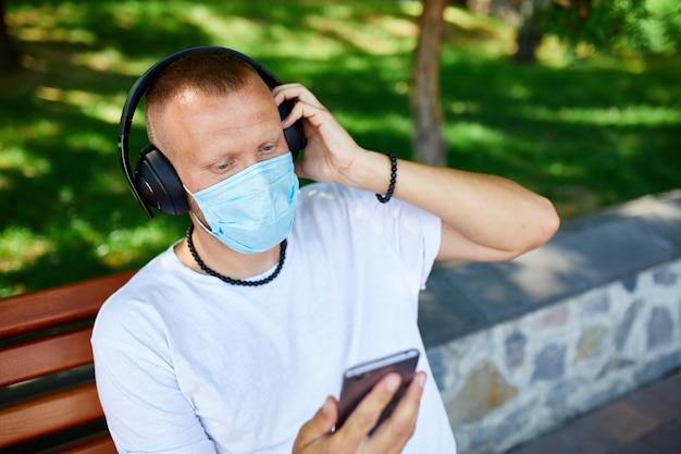 Mann, der musik mit kopfhörer hört, unter verwendung der smartphone tragenden gesichtsschutzmaske im freien im park, lebensstil neu normal, quarantäne, coronavirus