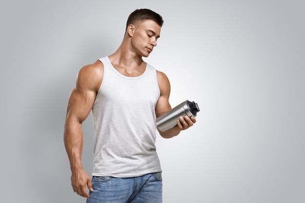 Mann der muskulösen eignung, der proteindrinkflasche hält