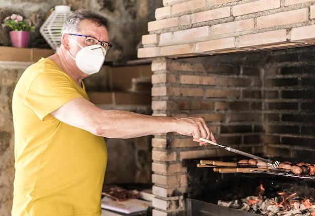 Mann, der nach dem coronavirus mit einer maske grillt