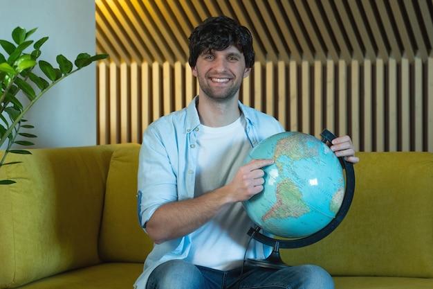 Mann, der nach ländern auf globus zu hause im wohnzimmer auf dem fröhlichen mann des sofas hält, der einen geografischen globus hält