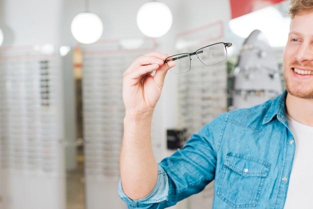 Mann, der nach neuen gläsern am optometriker sucht