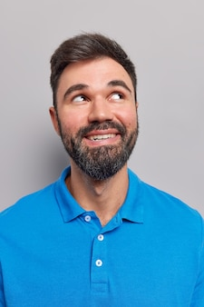 Mann, der nach oben schaut, denkt, dass etwas an einen angenehmen moment im leben erinnert, lächelt und zeigt zähne, trägt ein lässiges blaues t-shirt isoliert auf grau
