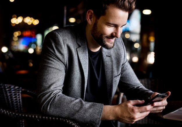 Mann, der nachrichten an seinem telefon liest