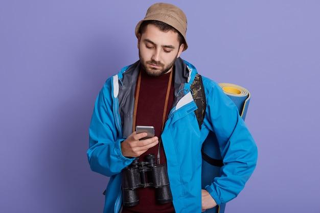 Mann, der nachrichten für seine familie von seinem handy während des wanderns sendet. reisender in hut und jacke mit handy-anwendung