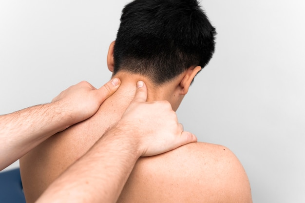 Mann, der nackenmassage für schmerzen vom physiotherapeuten erhält