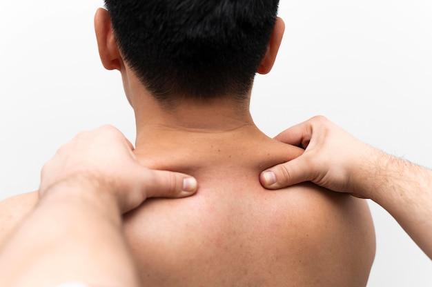 Mann, der nackenschmerzmassage vom physiotherapeuten erhält