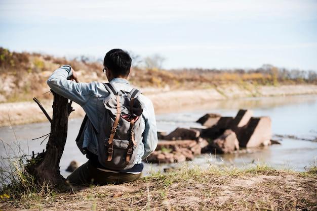 Mann, der nahe dem see sich entspannt