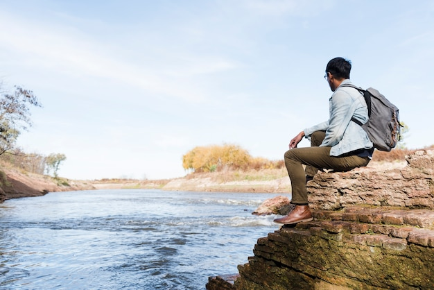 Mann, der nahe der seitenansicht des wassers sich entspannt