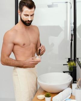 Mann, der natürliche bestandteile für eine gesichtsmaske verwendet