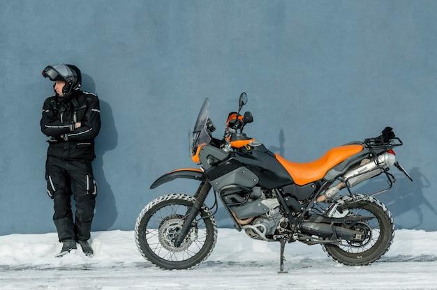 Mann, der neben motorrad mit helm steht
