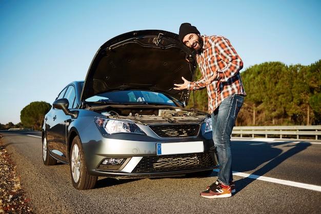 Mann, der neben seinem kaputten auto steht