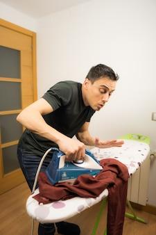 Mann, der nicht weiß, wie man kleidung bügelt, versucht erfolglos, ein hemd zu hause zu bügeln. mittlerer schuss.