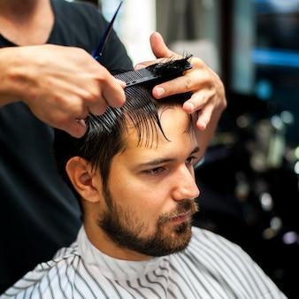 Mann, der noch beim erhalten eines haarschnitts sitzt
