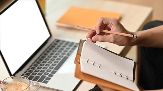 Mann, der notebook hält und zu hause mit laptop arbeitet.