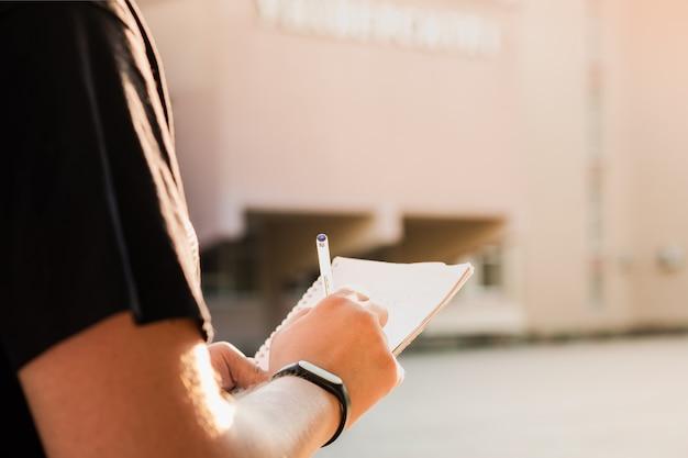 Mann, der notizen außerhalb einer bildungseinrichtung macht. die hände der jungen männlichen person, die einen notizblock und einen stift halten und informationen draußen schreiben
