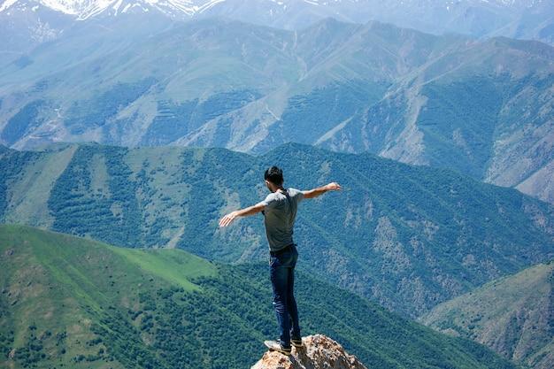 Mann, der oben auf einer klippe bei sonnenuntergang steht