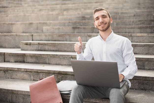Mann, der oben seinen großen finger beim sitzen auf treppe anhebt