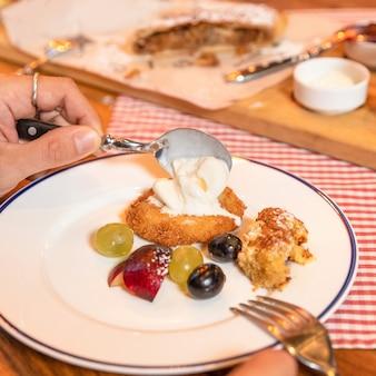 Mann, der obst, nachtisch, imbiss am restaurantabschluss oben isst