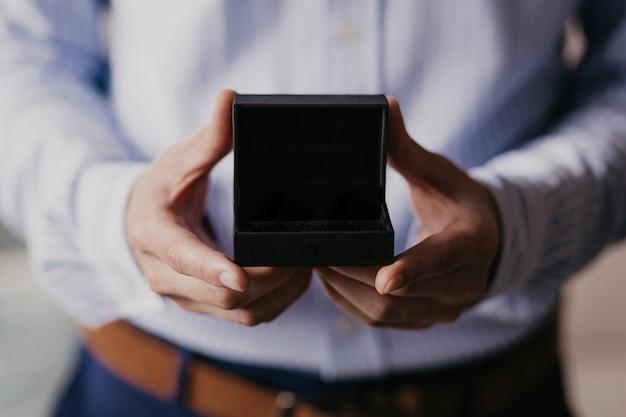 Mann, der offene schwarze geschenkbox hält