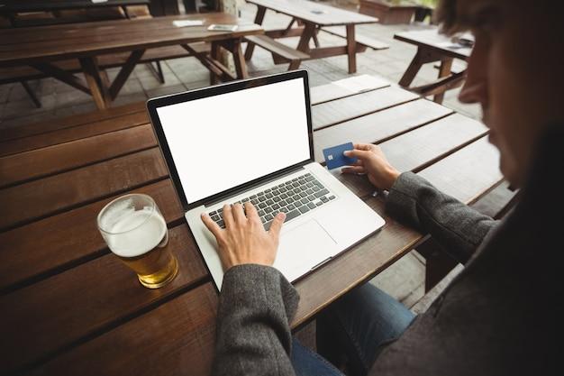 Mann, der online-einkauf mit kreditkarte auf laptop tut