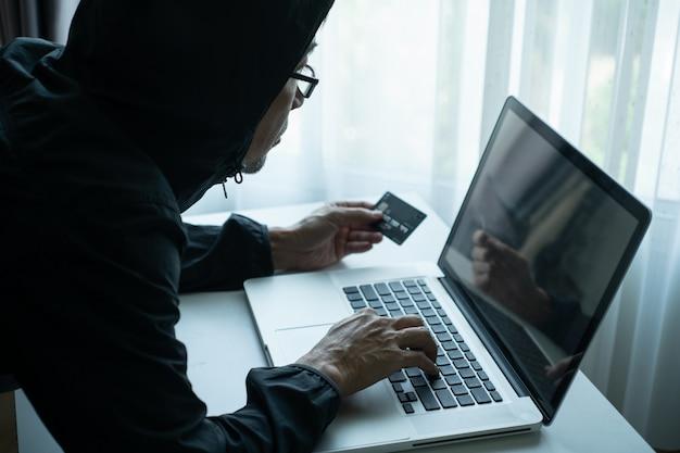 Mann, der online über laptop einkauft und mit kreditkarte bezahlt