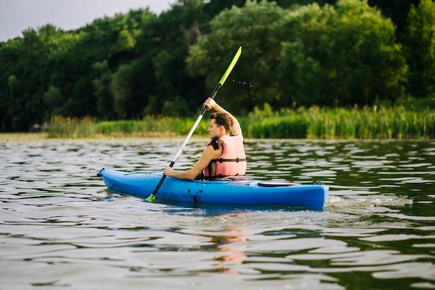 Mann, der paddel beim kayak fahren auf ruhigem see verwendet