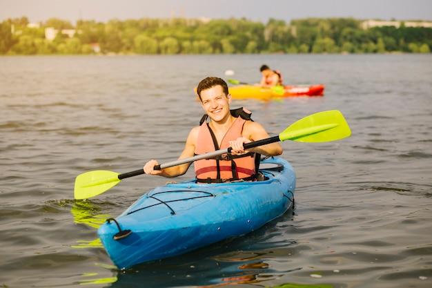 Mann, der paddel beim kayak fahren im wasser verwendet