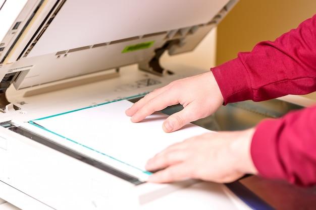 Mann, der papierblatt auf drucker für das scannen setzt.