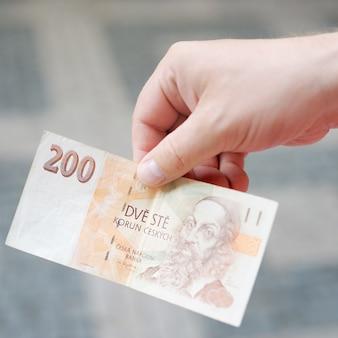 Mann, der papiergeld (tschechische krone) in seiner hand hält