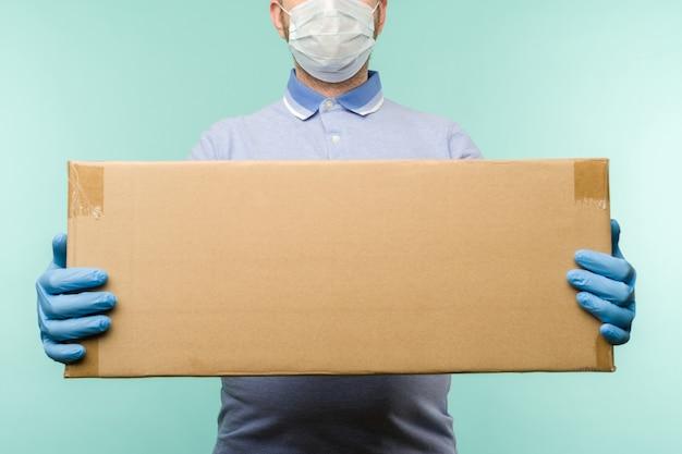 Mann, der pappkartons in den medizinischen gummihandschuhen und in der maske hält. coronavirus-pandemie-quarantäne-lieferkonzept