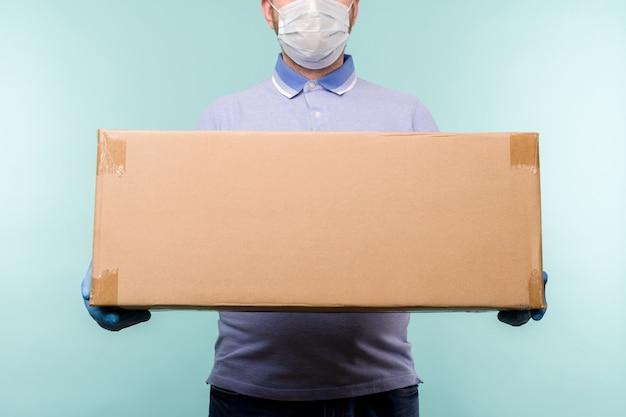 Mann, der pappkartons in den medizinischen gummihandschuhen und in der maske hält.