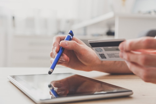 Mann, der pc-tablette mit stift und kreditkarte am tisch verwendet und online einkauft