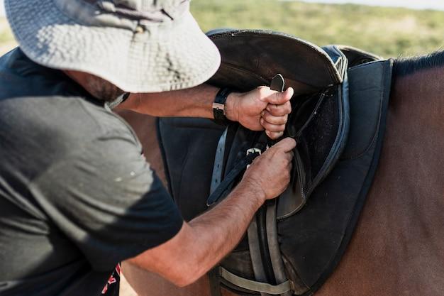 Mann, der pferd für fahrt vorbereitet
