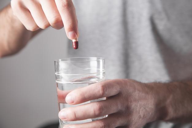 Mann, der pille und ein glas wasser hält.