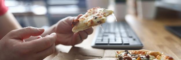 Mann, der pizza am arbeitsplatz im vorderen computer isst