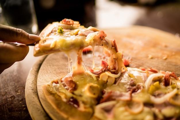 Mann, der pizza auf holztisch-, wurst- und mozzarellakäse, kopienraum hält.