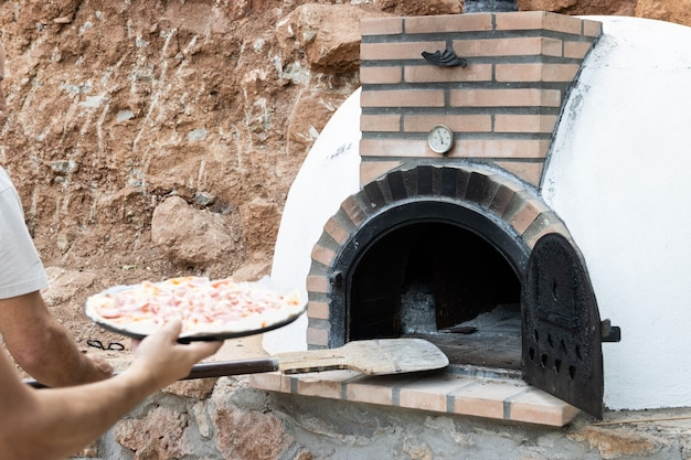 Mann, der pizza in handgemachten weiß lackierten holzofen legt, der im freien mit schaufel gebaut wurde, hintergrund